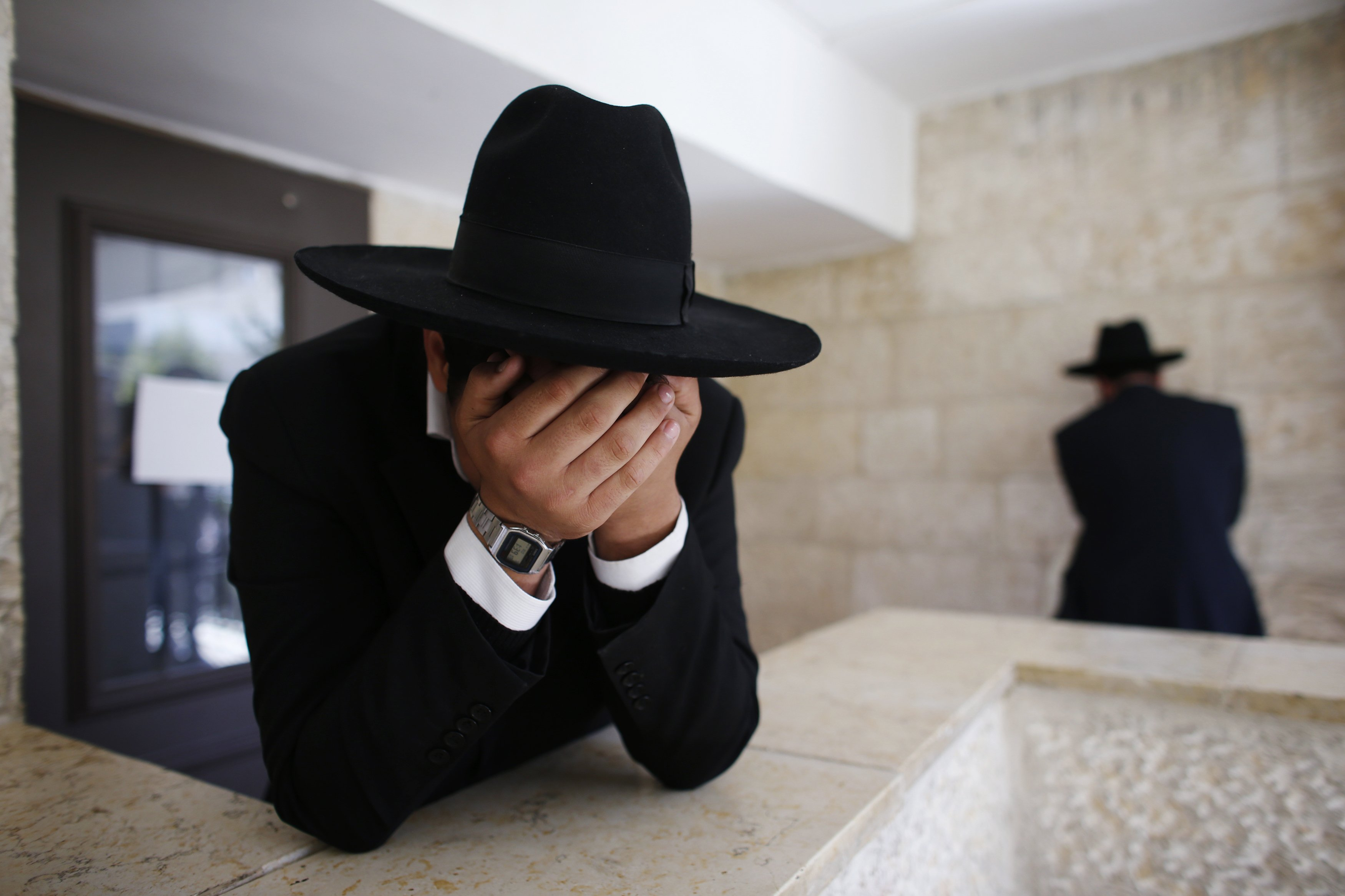 Ultra-Orthodox Jewish men react upon hearing the news about the death of Rabbi Ovadia Yosef, the spiritual mentor of the ultra-religious Shas political party, in Jerusalem October 7, 2013. Yosef, an Iraqi-born sage who turned an Israeli underclass of Sephardic Jews of Middle Eastern heritage into a powerful political force, died on Monday at the age of 93, plunging masses of followers into mourning. REUTERS/Ronen Zvulun (JERUSALEM - Tags: RELIGION OBITUARY TPX IMAGES OF THE DAY)